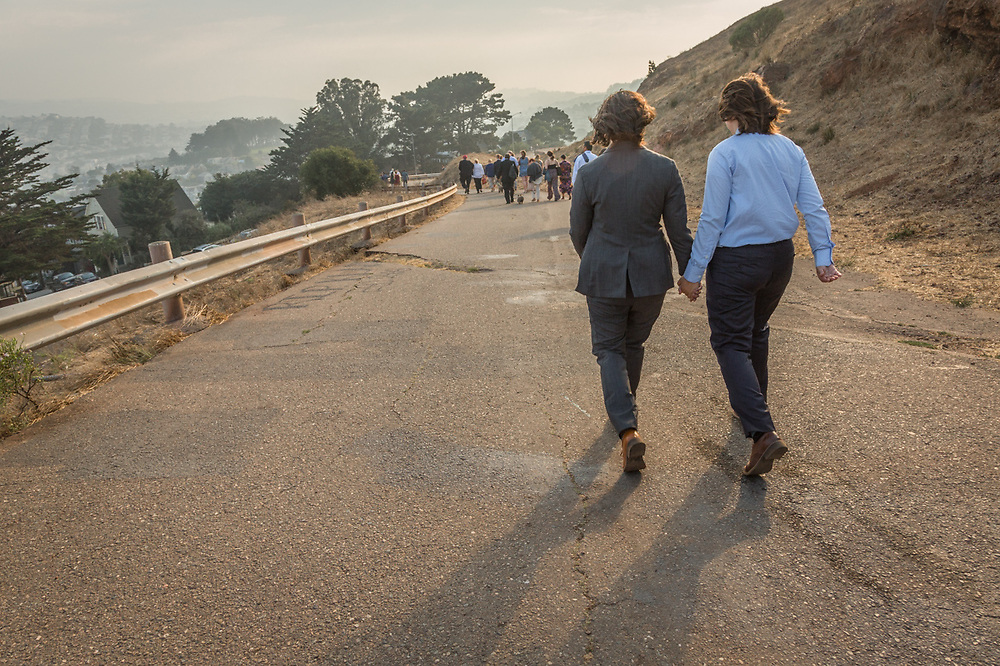 Olivia and Elyse walk together after their marriage atop Burnal Hill in San Francisco.