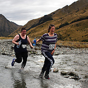 Runners Aishling Foley and Abigail Lang cross Moke Creek on the Ben Lomond High Country Station during the Pure South Shotover Moonlight Mountain Marathon and trail runs. Moke Lake, Queenstown, New Zealand. 4th February 2012. Photo Tim Clayton