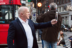 PICTURED: An irate commuter films anti-pollution protesters sitting on the road. Demonstrators from the anti-pollution group Stop Killing Londoners cause traffic chaos for London commuters as they conduct a series of short roadblocks at Marble Arch stopping cars and buses from entering Oxford Street and Park Lane. Irate motorists accused them of creating more pollution than they were stopping, whilst the group said their objectives were long term. A leaflet handed out to motorists says the government is not doing enough to tackle the crisis costing 'taxpayers and the NHS £billions [sic] a year'. PLACE, January 29 2018. © Paul Davey