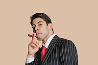 Portrait of a young businessman with red chili pepper imitating as smoking cigarette