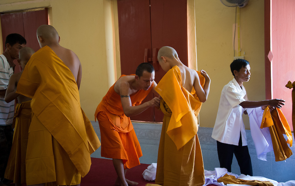 Young men are helped into the robes of a Buddhist monk in rural Nakhon Nayok, Thailand.