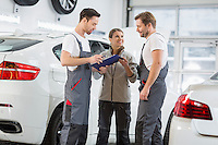 Automobile mechanics discussing over clipboard in car repair shop