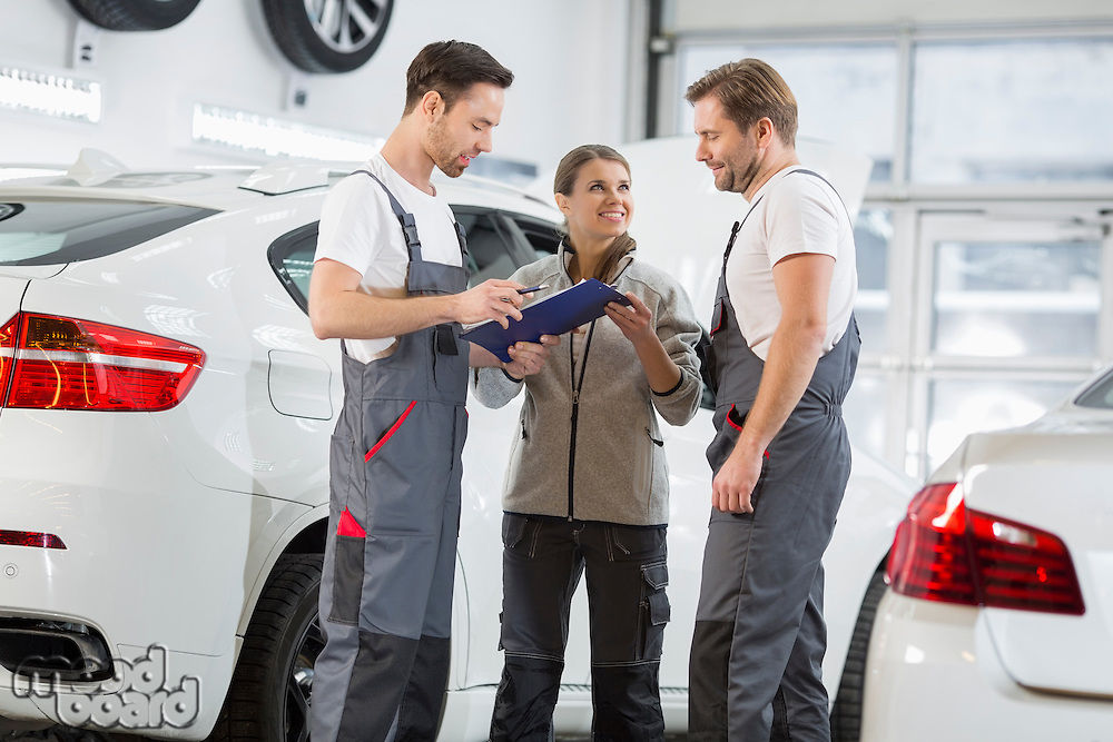Automobile mechanics discussing over clipboard in car repair shop