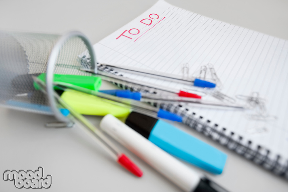 Close-up view of spiral notebook with to-do list and office supplies