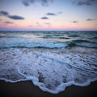 Ocean waves crashing on Miami Beach at sunset.
