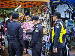August 1, 2018 - Bangkok, Thailand - A Bangkok code enforcement officer talks to a market vender on Khao San Road in Bangkok. Khao San Road is Bangkok's original backpacker district and is still a popular hub for travelers, with an active night market and many street food stalls. The Bangkok municipal government went through with it plans to reduce the impact of the street market on August 1 because city officials say the venders, who set up on sidewalks and public streets, pose a threat to public safety and could impede emergency vehicles. Venders are restricted to working from 6PM to midnight and fewer venders will be allowed to set up on the street. It's the latest in a series of night markets and street markets the city has closed. (Credit Image: © Sean Edison via ZUMA Wire)