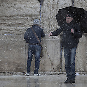 Two men are seen as snow and rain fall at The Western Wall on January 7, 2015 in Jerusalem, Israel. (Photo by Elan Kawesch)