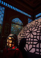 Little Uyghur girl in Sultan Saiyidhan Tomb in Yarkand, Xinjiang Uyghur autonomous region, China. The tombs of Sultan Saiyidhan are protected in<br /> small carved wooden houses<br /> that let the last rays of the sun<br /> seep through.