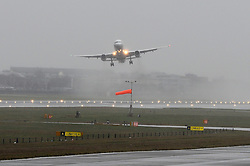 A plane looks uneven in the air as it takes off despite heavy rain and strong winds at Heathrow's Terminal 5.<br /> Christmas travellers leave for their festive holidays at Heathrow Airport. Monday, 23rd December 2013. Picture by Ben Stevens / i-Images