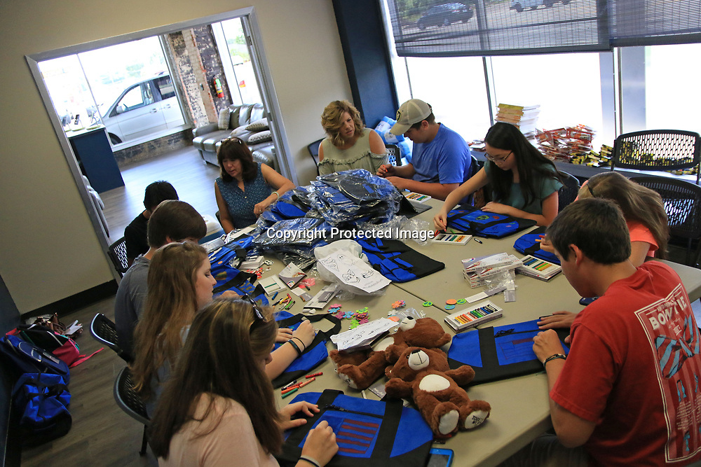 A Group of local teenagers work to decorate supply bags which will go to children in foster care as part of the Together We Rise organization.