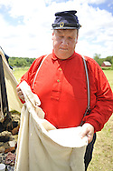 Old Bethpage, New York, USA - July 21, 2012: ROBERT WALKER of Coram, NY wearing  a red wool military shirt  shows the off-white wool undershirt soldiers wore, as he portrays a Private, at re-creation of Camp Scott, a Union Army training camp, at Old Bethpage Village Restoration, to commemorate 150th Anniversary of American Civil War, on Saturday, July 21, 2012.
