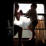 Two children watch the scenary outside the window of a Trans-Siberian railroad car.