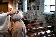 Belgium - Liege April 04, 2007, Priest lays his hand on the woman's head during a mass at St-Martin Basilica ©Jean-Michel Clajot