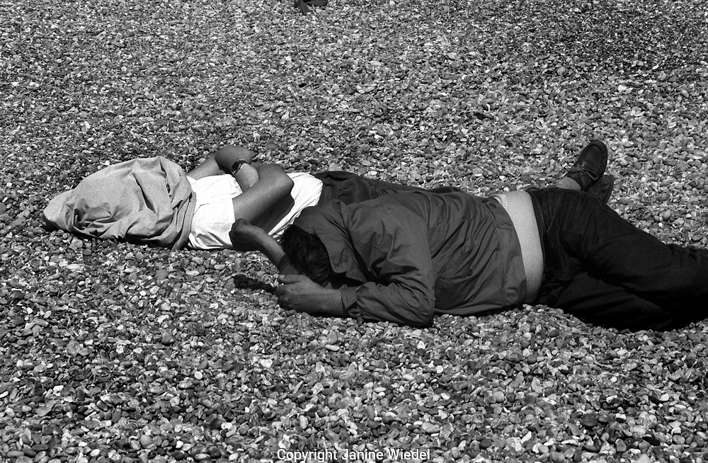 Asleep covered up against the sun on the pebble beach at Dover
