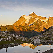 Heather Goodrich walks across boulders with Mount Shuksan reflected in a glacier tarn.