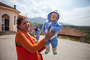 Proud Roma mother holding her child and posing for a portrait at the Roma part of the city of Vinica in Macedonia during the European Immunization Week.