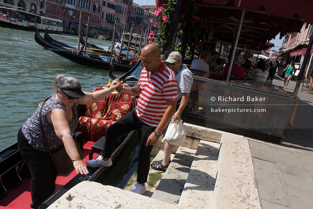 A gondoliers helps an insteady tourist from his boat, after ride on the Grand Canal in Venice, Italy. Current prices (2015) is 80 Euros for a 40-minute journey (earning them approx 130,000 Euros a year) along the waterways of this old city but rarely do gondoliers wear their straw hat.