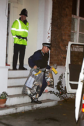 © Licensed to London News Pictures . 09/10/2012 . Altrincham , UK . A policeman carries evidence bags full of cassettes from 1 Woodlands Road , Altrincham , Cheshire . Police arrested Jimmy Savile's former chauffeur , Ray Teret , and housemate Alan Ledger , yesterday (8th November) over historic child rape allegations . Photo credit : Joel Goodman/LNP
