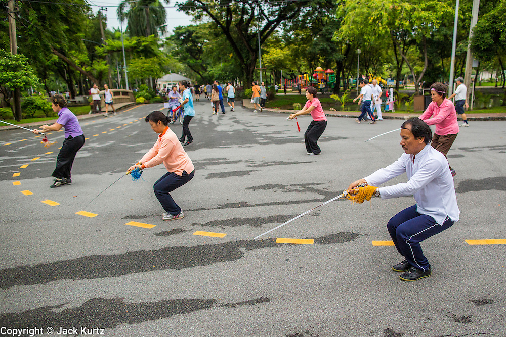 06 OCTOBER 2012 - BANGKOK, THAILAND:  People do Tai Chi exercises with ceremonial swords in Lumphini Park in Bangkok. The Thai government promotes exercise classes as a way staying healthy. Lumphini Park is 142 acre (57.6-hectare) park in Bangkok, Thailand. This park offers rare open public space, trees and playgrounds in the congested Thai capital. It contains an artificial lake where visitors can rent boats. Exercise classes and exercise clubs meet in the park for early morning workouts and paths around the park totalling approximately 1.55 miles (2.5km) in length are a popular area for joggers. Cycling is only permitted during the day between the times of 5am to 3pm. Smoking is banned throughout smoking ban the park. The park was created in the 1920's and named after Lumbini, the birthplace of the Buddha in Nepal.   PHOTO BY JACK KURTZ