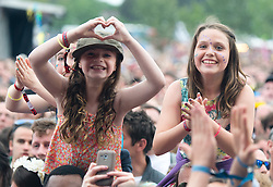© Licensed to London News Pictures. 14/06/2015. Isle of Wight, UK.  Young girls watch Paolo Nutini perform at Isle of Wight Festival 2015 on Sunday Day 4.  Yesterday suffered torrential rain all afternoon and evening, after a first day of warm sun.  This years festival include headline artists the Prodigy, Blur and Fleetwood Mac.  Photo credit : Richard Isaac/LNP