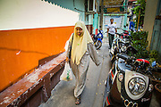 """11 JANUARY 2013 - BANGKOK, THAILAND:    A Muslim woman walks through the Ban Krua neighborhood in Bangkok. The Ban Krua neighborhood of Bangkok is the oldest Muslim community in Bangkok. Ban Krua was originally settled by Cham Muslims from Cambodia and Vietnam who fought on the side of the Thai King Rama I. They were given a royal grant of land east of what was then the Thai capitol at the end of the 18th century in return for their military service. The Cham Muslims were originally weavers and what is known as """"Thai Silk"""" was developed by the people in Ban Krua. Several families in the neighborhood still weave in their homes.             PHOTO BY JACK KURTZ"""