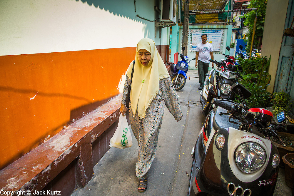 "11 JANUARY 2013 - BANGKOK, THAILAND:    A Muslim woman walks through the Ban Krua neighborhood in Bangkok. The Ban Krua neighborhood of Bangkok is the oldest Muslim community in Bangkok. Ban Krua was originally settled by Cham Muslims from Cambodia and Vietnam who fought on the side of the Thai King Rama I. They were given a royal grant of land east of what was then the Thai capitol at the end of the 18th century in return for their military service. The Cham Muslims were originally weavers and what is known as ""Thai Silk"" was developed by the people in Ban Krua. Several families in the neighborhood still weave in their homes.             PHOTO BY JACK KURTZ"