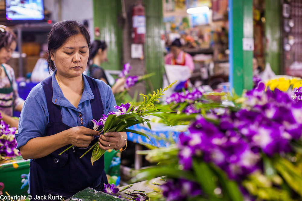19 OCTOBER 2012 - BANGKOK, THAILAND:   Vendors make floral arrangements in the Bangkok Flower Market. The Bangkok Flower Market (Pak Klong Talad) is the biggest wholesale and retail fresh flower market in Bangkok.  The market is busiest between 3:30AM and 6AM. Thais grow and use a lot of flowers. Some, like marigolds and lotus, are used for religious purposes. Others are purely ornamental.      PHOTO BY JACK KURTZ