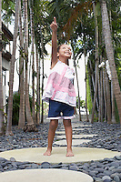 Girl (5-6 years) standing on stepping stone on path pointing up