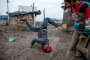 A young man showing his break dance skills on a muddy patch of ground in the middle of the Roma settlement located in 'Budulovska street' in  Moldava nad Bodvou (2012). The city has roughly 11200 inhabitants, about 1980 (18%) of them have Roma ethnicity and around 800 are living at the segregated settlement 'Budulovska Street' (2014).
