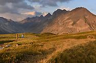 Ein Mann und eine Frau wandern auf dem Cuolm da Latsch oberhalb Berg&uuml;n im Albulatal mit Blick ins Val Stugl und die Gipfel der Ducans, Parc Ela, Graub&uuml;nden, Schweiz<br /> <br /> A man and a female are hiking on the Cuolm da Latsch above the village Berg&uuml;n in the Albula Vally with the view on the Val Stugl und the peaks of the Ducans, Parc Ela, Grisons, Switzerland