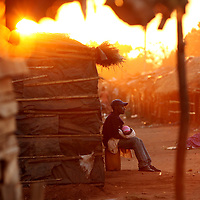 A man holds a baby as the sun sets on the closing hour of an informal market in Chimoio, Mozambique.