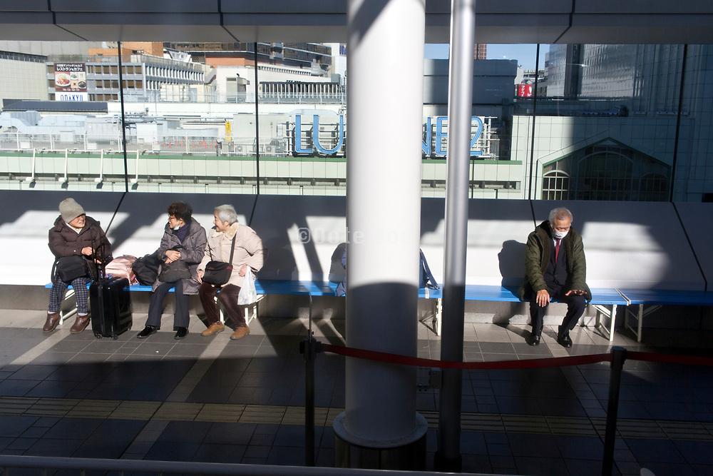 elderly people waiting at the Shinjuku bus station in Tokyo