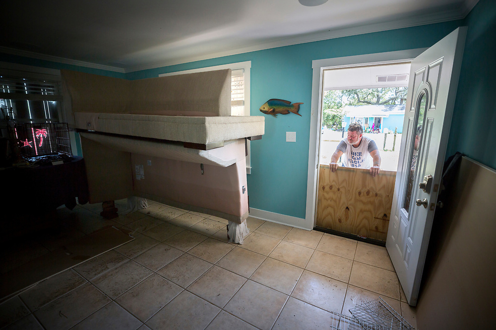 Joey Spalding removes the plywood from his front door after three feet of water flooded his house, Tuesday, Sept., 12, 2017, on Tybee Island, Ga. (AP Photo/Stephen B. Morton)