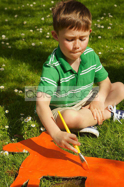 Boy Painting Cardboard Cut Out in Garden