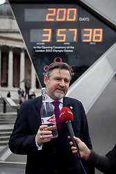 © Licensed to London News Pictures. 09/01/2012. London, U.K...Labour MP for Brent North, Barry Gardiner, holds a rally at Trafalgar Square in front the the 2012 Olympic countdown clock, inviting Lord Sebastian Coe to drink the water from Bhopal. To coincide with the 27th anniversary of the disaster Labour Friends of India today hold the event urging LOGOC to drop Dow Chemical Company as a partner of the 2012 Olympic Games. The labour MP holds up a bottle of water named B'EAU PAL..Photo credit : Rich Bowen/LNP