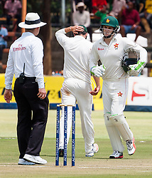 Zimbabwe wicket keeper Peter Moor runs past team captain Graeme Cremer with hand on head during the 100th test match played by Zimbabwe in a match with Sri Lanka at Harare Sports Club 29 October 2016.