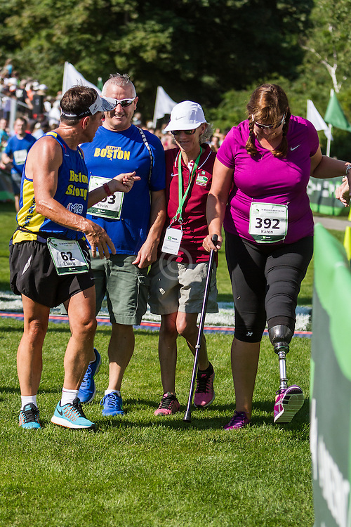 Karen Rand McWatters, victim in Boston Marathon bombings, finishes accompanied by husband Kevin, greeted by Joan Samuelson and Dave McGillivray