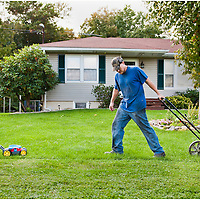 Four-year-old Wyatt Fritz, left, helps his father Ash Fritz with the lawn chores outside their home on Monday, Sept. 26, 2011, in Shanksville, Pa.
