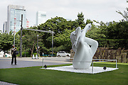 man making a picture of a sculpture by Marc Quinn in front of The national Museum of Modern Art Tokyo