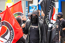 "Cricklewood, London, July 19th 2014. Masked anti-fascist activists  counter-protest the anti-Islamist ""South East Alliance"" as they demonstrate outside the London offices of Egypt's Muslim Brotherhood."