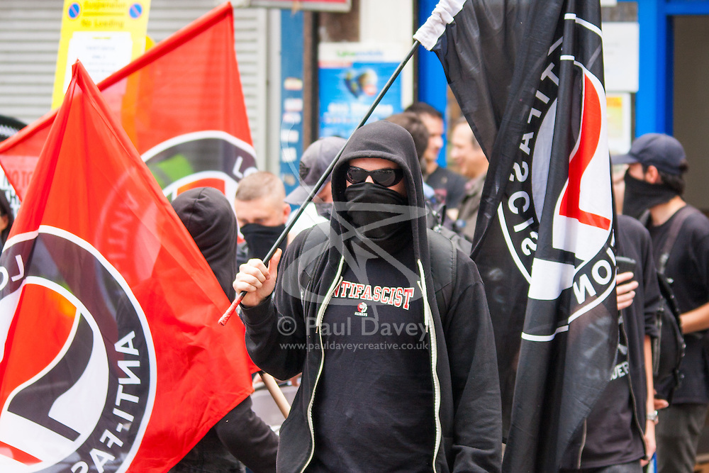 """Cricklewood, London, July 19th 2014. Masked anti-fascist activists  counter-protest the anti-Islamist """"South East Alliance"""" as they demonstrate outside the London offices of Egypt's Muslim Brotherhood."""