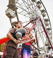 """Charlie and Scarlett carry an accumulation of """"prizes"""" from midway games at the Sandwich Fair Saturday afternoon.   (Karen Bobotas/for the Laconia Daily Sun)"""
