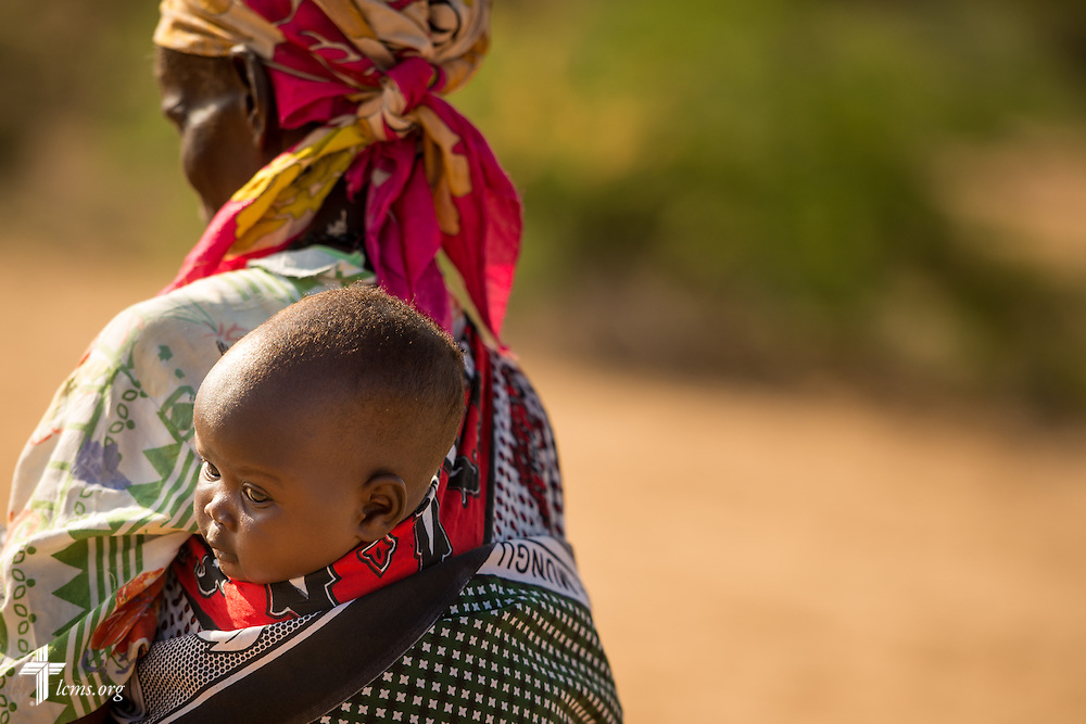 A woman carries a young child from the LCMS Mercy Medical Team on Monday, June 20, 2016, in Nataparkakono, a village in Turkana, Kenya.  LCMS Communications/Erik M. Lunsford