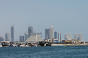 The landmark pyramid of Sheraton Doha hotel, dhows in front of the skyline of Western Corniche.