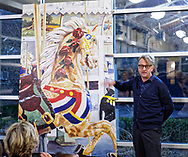 Garden City, New York, USA. March 9, 2019. Artist MICHAEL WHITE stands next to his mural (approximatey 7 feet by 5 feet, of a closeup of the lead horses of Nunley's Carousel during Unveiling Ceremony of mural. Elected officials and members of Baldwin Civic Association and Baldwin Historical Society, and others, also gave speeches during the event, held at historic Nunley's Carousel in its Pavilion on Museum Row on Long Island.