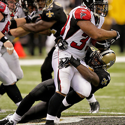 2009 November 02:  Atlanta Falcons running back Michael Turner (33) is tackled by New Orleans Saints linebacker Jo-Lonn Dunbar (56) in the first half during a 35-27 win by the Saints over the Falcons at the Louisiana Superdome in New Orleans, Louisiana.