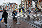 Op het Muntplein in Amsterdam rijdt een meisje op een snorscooter over het fietspad. Voetgangers steken over.<br /> <br /> A girl rides on a scooter on the bicycle lane at the Munt Square in Amsterdam. Pedestrians are crossing the street.