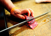 A retailer cuts up blue fin tuna at the world's largest fish and marine products market in Tsukiji, Tokyo