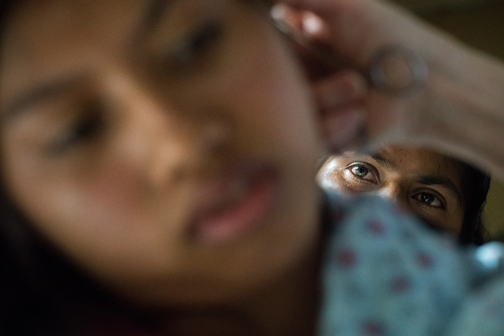 Anabis Vera Gonzales, a volunteer with Central American Medical Outreach, inspect the ear of a patient the day following surgery at Occidente Hospital in Santa Rosa de Copan, Copan, Honduras March 1, 2017. Photo Ken Cedeno