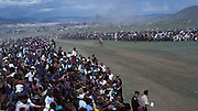 Mongolia, Ulaan Baator. July 1996: Spectators on horses line the finish  at one of the horse races in the Naadam Festival. The annual festival celebrates the three traditional sports of horse racing, archery and wrestling.